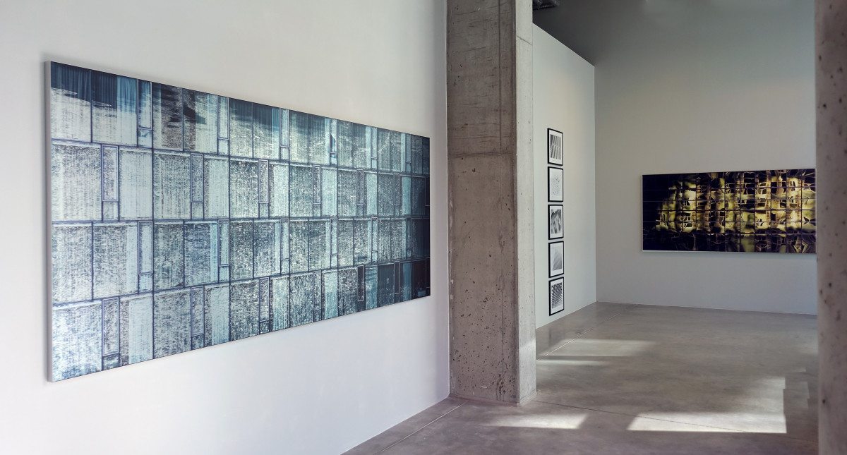 New York #10. 107x255 cm.<br /> A picture opens up<br /> Elise Schonhowd, artist<br /> May 2017<br /> When a picture takes shape, and becomes a new work of art, it involves both processes the artist was conscious of already and others that are discovered along the way. Those who encounter the piece for the first time when it is displayed on a wall, experience the same thing. Capturing a moment in time on camera is the point of departure for something that does more than merely reflect the subject of the picture, in this case a modern building. The motif may have presented itself, so to speak, if one ventures to personalise the processes on both ends a bit.  A series of events occurs when a motif catches someone's attention, first the photographer's and then later, after many stages, the attention of people who visit the gallery. The image is seen from a distance, large. The bottom part gleams. The vibrant surface of the brushed aluminium is infused with a quality that could initially perhaps be described as slightly dry denim. A moving level appears and draws the audience closer in a natural manner. The picture follows the observer's movements as the light changes. It hangs there on the wall, narrow and elegant, and gives an immediate impression of orderly structure. Some may perceive it as totally abstract. You see lines, you see vertical surfaces, repeating sections and perhaps the experience at this point triggers associations to minimalistic music. This is because of the repetition. Or because? Why because? Does using the word mean that you subsequently discover you have only seen a tiny portion, because there is also a lot to be seen within the surface? A closer look reveals a vibrant exchange, a meeting between the material at the bottom and the fluid-looking pattern above. At this point the experience can be almost confusing, because even though the eye picks up on the first thing that is at odds with the solidity of the architecture – it takes a while before
